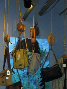 Hand bags hang from the ceiling adding to atmosphere as customers check out.